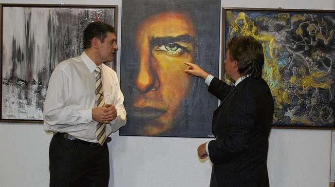 Doris Hirsch - Dieter Weisenborn (links) erläutert Bürgermeister Rastetter die Entstehung des Porträts mit den Augen von Tom Cruise und dem Mund von Daniel Craig.