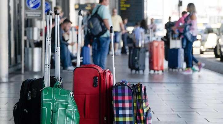 Fluggäste warten in Hamburg neben ihrem Gepäck.